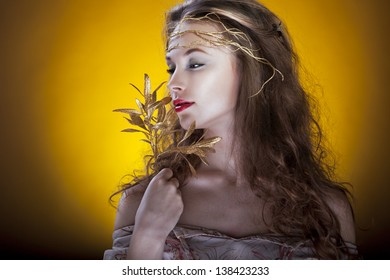 Girl with a gold branch in hair on yellow background studio shot