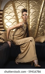 girl in gold dress sitting on chair