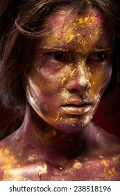 Girl with gold paint on face with face art and body art. Black hair. Portrait of sexy woman on dark background