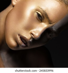 Girl with gold and silver skin in the image of an Oscar. Art image beauty face. Picture taken in the studio on a black background.