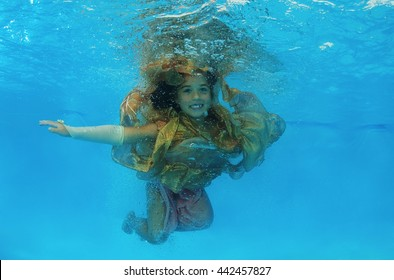 Girl in a golden dress under water in the pool