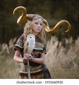 Girl with golden horns and an owl barn owl in the autumn forest