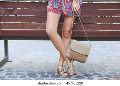 Girl in golden leather sandals,red dress and beige leather handbag in hand. Woman in summer street look walking around the city on sunny summer day. Young fashion model posing outdoors.