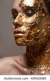 girl with golden makeup and gold foil on the face