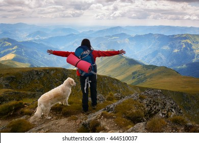 Girl with a golden retriever dog on top of a mountain watching a beautiful landscape with arms wide open