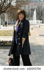 Girl in a good mood is walking around the city. She has brown hair and a bob hairstyle, she is wearing a blue raincoat and a scarf around her neck.