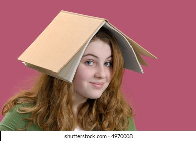 Girl goofing around with book on her head instead of studying