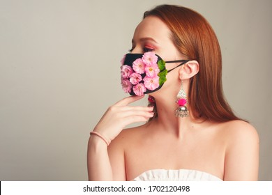 Girl with gorgeous long hair in an antiviral mask. Fashion photo on the cover of the magazine. Pandemic, virus, coronavirus, masked girl spring has come. Spring fashion, model in a mask of flowers