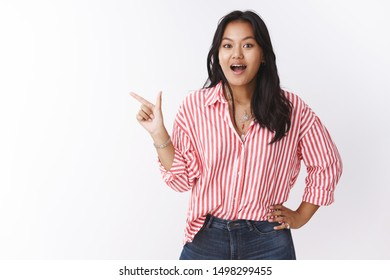 Girl gossiping about coworker pointing left astonished and speechless drop jaw from amazement and surprised holding hand on waist looking stunned at camera under great impression over white wall