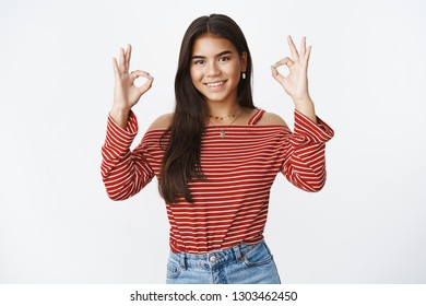 Girl got deal under control. Portrait of confident assuring and assertive charming young teenager in blouse showing okay gesture as saying everything perfect, smiling pleased with good result