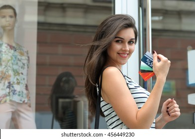 Girl got a good deal. She smiles holding discount card in her hand against the glass storefront