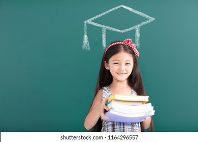 girl in graduation cap with books standing before  chalkboard