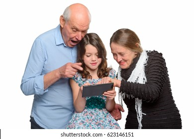 Girl and grandparents browsing through family photos on tablet. Granny and grandad wake memories and show an old shot to their granddaughter.