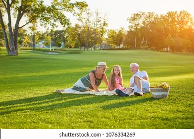 Girl with grandparents having picnic. People relaxing in summer park.