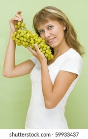 The girl with grapes on a green background