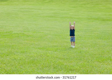 girl in the grass with arms up plenty of room for copy