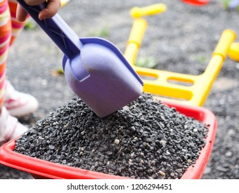 Girl with gravel, shovel and wheelbarrow, at close up