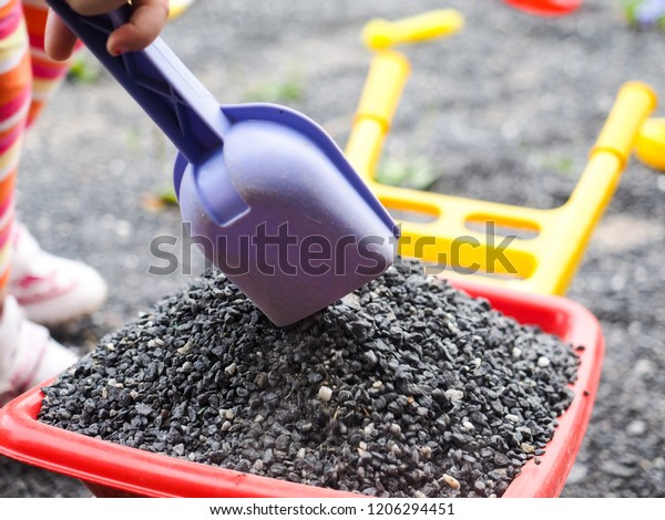 Girl with gravel, shovel and wheelbarrow, at close up