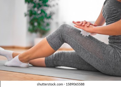 Girl in gray tracksuit with massage ball in her hands sits on rug in gym