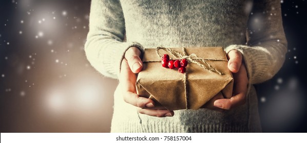 girl in a gray warm winter sweater, holding a New Year or Christmas gift, on a blurry background, space for text