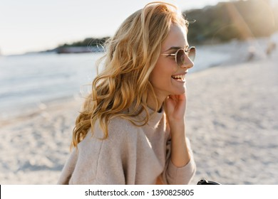 Girl in great mood enjoys sunny spring day at sea. Blonde in cashmere outfit holding cup of tea