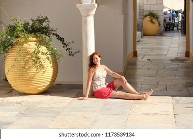girl in a Greek yard on the background of a flowerpot
