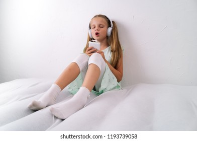 A girl in a green dress listens to music from a smartphone in large white headphones and sings along on a white background.