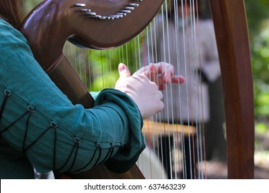 Girl in green dress plays on a Celtic harp in the summer garden