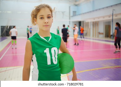 Girl in green poses with ball in gym during volleyball game, playing people out of focus