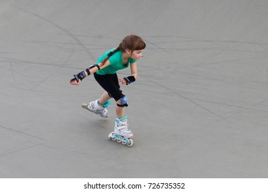 Girl in green roller skates on sport playground with ramps at summer day