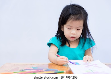 Girl in green shirt was sitting and coloring it with wood paint on drawing paper. Child 3-4 years old have fun making crafts. Kid do art on wooden table, train their imagination. White wall background