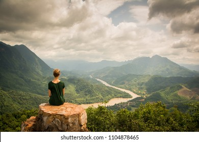 Girl with green shirt sitting on a rock on top of a mountain watching the beautiful scenery of the backcountry of Nong Khiaw, Laos. Location: Viewpoint in Nong Khiaw.