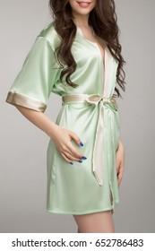 Girl in green silk robe, on gray background