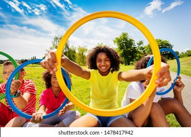 Girl in group of kids look through colorful hoop