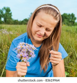 The girl guesses on a camomile, sitting on a green grass