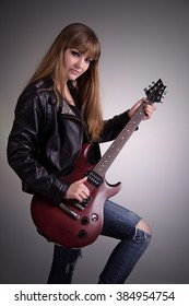 Girl with a guitar, leather jacket, bright makeup, electric guitar mahogany, standing with his guitar, vertical composition, stringed musical instrument, female feet.