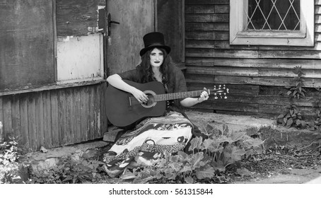 The girl with a guitar stays near old building. Extravagant street guitarist in hat playing guitar