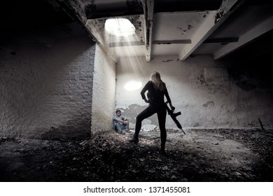 A girl with a gun guards a hostage in the basement of the ruins of a house.