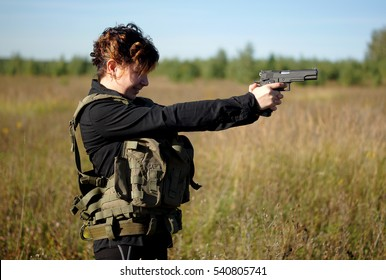 A girl with a gun in his hands.Outdoor portrait