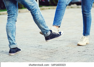 Girl and guy bump feet outdoors. Coronavirus epidemic. Foot shake style of greetings. Coronavirus prevention. Covid 19 prevention. People, lifestyle 2020. Young couple greeting with foot.
