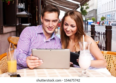 Girl with a guy in a cafe used  tablet computer