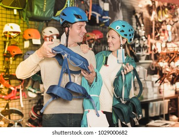 Girl and the guy choosing at a shop of sports equipment a mountaineering equipment. Focus on man