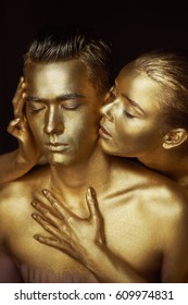 A girl and a guy covered in gold paint. With my eyes closed.The girl leaned in and kisses his ear