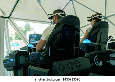A girl and a guy with glasses of virtual reality are sitting in a moving interactive chair. Virtual games. The concept of virtual reality and cyberspace.