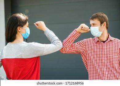 Mädchen und Junge grüßen mit Ellbogen im Freien. Neues wirkliches Leben. Coronavirus-Quarantäne. Coronavirus-Epidemie. Freunde in der Sicherheitsmaske draußen. Junge Paare tragen im Freien Gesichtsmasken.Soziale Distanzierung.