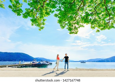 girl and guy are holding hands on the shore of a mountain lake. pier with boats