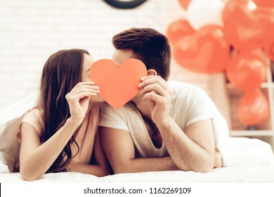 A Girl And A Guy Kiss. Red Heart Origami Concept. Love Each Other. Romantic Holiday. Sweetheart's Celebration Concept. Young And Handsome. Happy Relationship. Feelings Showing. Holding Together.