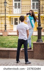 Girl and guy on the streets of European cities. Couple walking along the picturesque street. They look at the sights. Travel, couple, city, map, beauty, walk - travel concept. Article about Travel