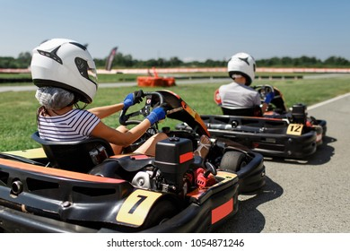 Girl with a guy riding a go-kart. outdoor activities in summer