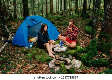 girl with a guy sitting near a tent in the woods
